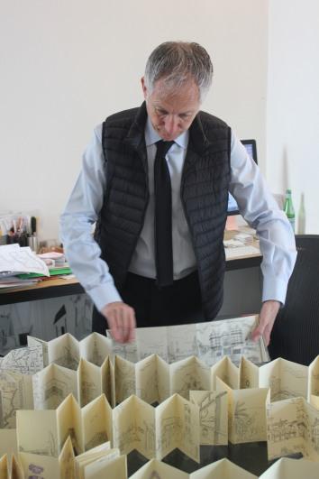 Bernardo Gómez-Pimienta presentando sus dibujos sobre la mesa 'Lore' de su autoría.